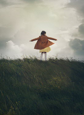 Mark Owen LITTLE GIRL IN COAT PLAYING IN WINDY FIELD Children