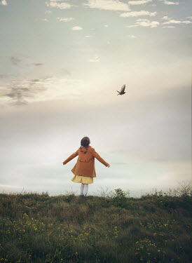 Mark Owen LITTLE GIRL STANDING IN FIELD WATCHING BIRD Children
