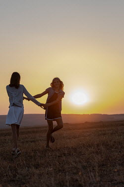 Galya Ivanova TWO YOUNG GIRLS PLAYING IN FIELD AT SUNSET Children