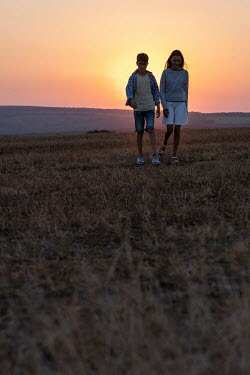 Galya Ivanova YOUNG BOY AND GIRL WALKING IN SUNLIT FIELD Children