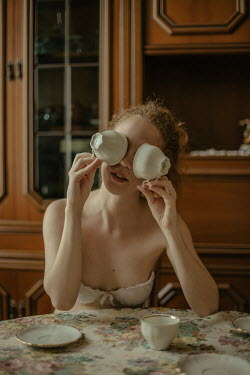Irene Gittarelli WOMAN COVERING EYES WITH TEACUPS INDOORS Women