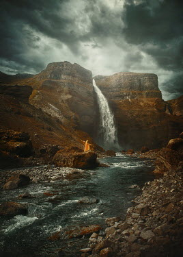 Terrence Drysdale WOMAN IN CAPE BY WATERFALL WITH STORMY SKY Women