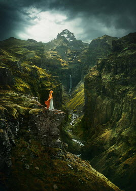 Terrence Drysdale WOMAN IN CAPE ON CLIFFS WITH WATERFALL Women