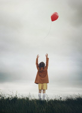 Mark Owen LITTLE GIRL PLAYING WITH BALLOON IN FIELD Children