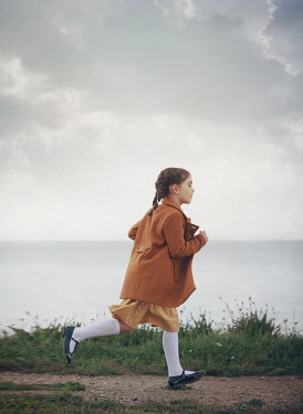 Mark Owen LITTLE GIRL WITH COAT RUNNING BY SEA Children