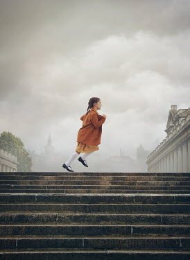 Mark Owen LITTLE GIRL RUNNING BY GRAND BUILDINGS IN CITY Children