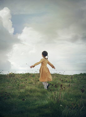 Mark Owen LITTLE GIRL PLAYING IN FIELD BY SEA Children