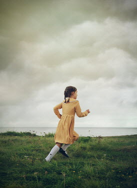 Mark Owen LITTLE GIRL IN DRESS RUNNING BY SEA Children