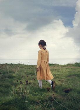 Mark Owen LITTLE GIRL IN DRESS WALKING BY SEA Children
