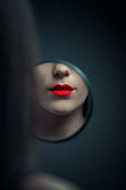 Ildiko Neer Woman's red lips reflecting round mirror