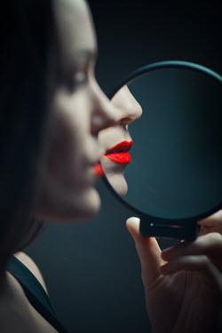 Ildiko Neer Woman's red lips reflecting round mirror