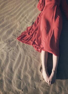Mark Owen BAREFOOT WOMAN IN RED DRESS LYING ON SAND Women