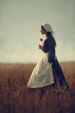 Magdalena Russocka historical maid with poppy standing in field