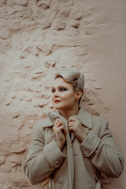 Nic Skerten blonde retro woman wearing beige trenchcoat
