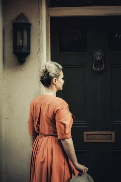 Nic Skerten BLONDE WOMAN IN DRESS WAITING OUTSIDE HOUSE Women