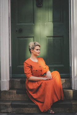 Nic Skerten retro woman in orange dress sitting on steps