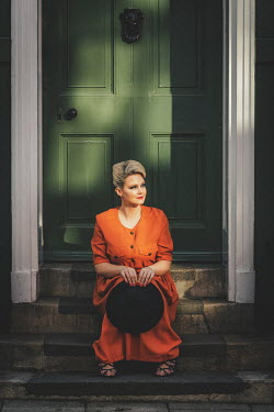 Nic Skerten retro woman wearing orange dress sitting on steps