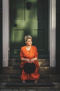 Nic Skerten BLONDE WOMAN IN DRESS SITTING OUTSIDE HOUSE Women