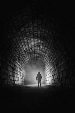 Andrei Cosma SILHOUETTED MAN STANDING IN DARK TUNNEL Men