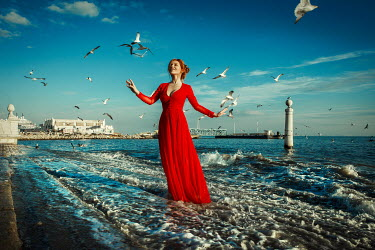 Katerina Klio WOMAN WITH RED DRESS STANDING IN SEA WITH BIRDS Women