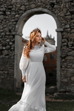 Katerina Klio WOMAN IN WHITE OUTDOORS BY STONE ARCH Women