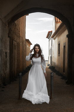 Katerina Klio WOMAN IN WHITE IN STREET UNDER ARCHWAY Women