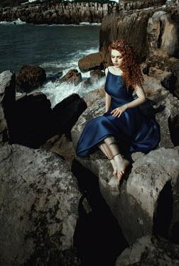 Katerina Klio WOMAN WITH CROWN SITTING ON ROCKS BY SEA Women