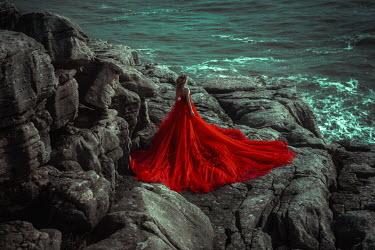 Katerina Klio WOMAN IN RED FLOWING GOWN ON ROCKS BY SEA Women