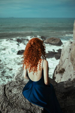 Katerina Klio WOMAN WITH RED HAIR SITTING ON ROCK BY SEA Women