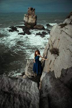 Katerina Klio WOMAN WITH RED HAIR STANDING ON ROCK BY SEA Women