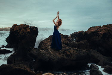 Katerina Klio WOMAN WITH RED HAIR STRETCHING ON ROCKS BY SEA Women