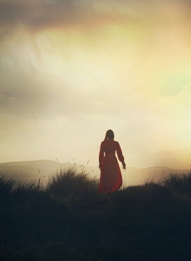 Mark Owen WOMAN IN RED DRESS WALKING IN DUNES AT SUNSET Women