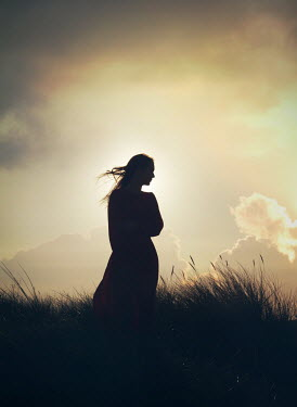 Mark Owen SILHOUETTED WOMAN IN WINDY FIELD AT SUNSET Women