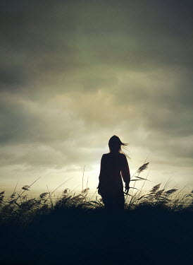 Mark Owen SILHOUETTED WOMAN IN GRASS WATCHING SEA AT DUSK Women