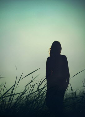 Mark Owen SILHOUETTED WOMAN STANDING IN GRASS AT DUSK Women