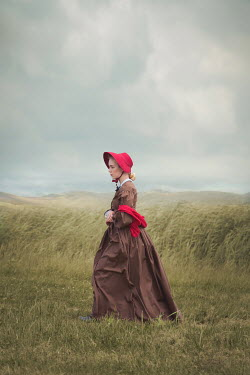 Joanna Czogala WOMAN WITH BONNET WALKING IN WINDY FIELD Women