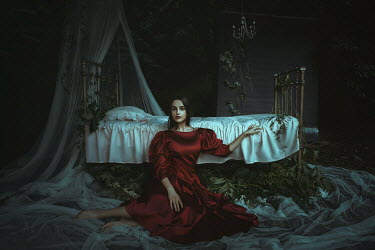 Katerina Klio WOMAN IN RED SITTING BY BED IN GARDEN Women