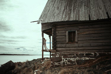 Katerina Klio WOMAN STANDING BY WOODEN CABIN NEAR LAKE Houses