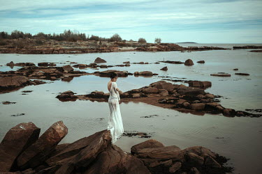 Katerina Klio WOMAN IN WHITE DRESS ON ROCKS BY WATER Women