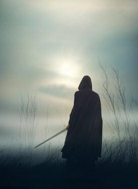 Mark Owen MAN IN CAPE HOLDING SWORD IN FOGGY FIELD Men