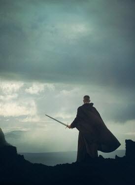 Mark Owen MAN IN CAPE HOLDING SWORD IN COUNTRYSIDE AT DUSK Men