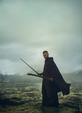 Mark Owen MAN IN CAPE HOLDING STAFF AND SWORD IN BLEAK LANDSCAPE Women