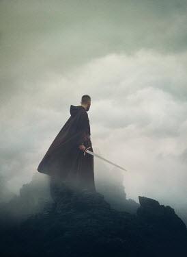 Mark Owen MAN IN CAPE HOLDING SWORD ON FOGGY CLIFF Men