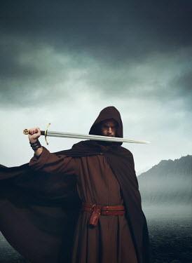Mark Owen MAN WITH CAPE HOLDING SWORD IN STORMY LANDSCAPE Men