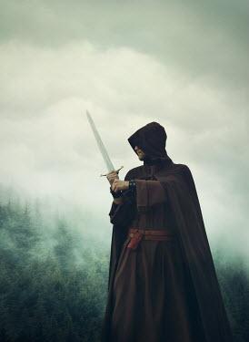 Mark Owen MAN IN CAPE HOLDING SWORD IN FOGGY COUNTRYSIDE Men