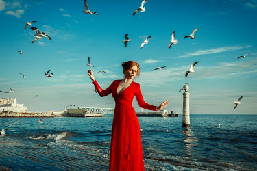 Katerina Klio WOMAN WITH RED DRESS STANDING BY SEA WITH BIRDS Women