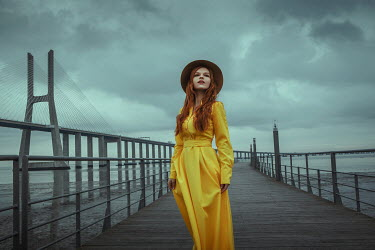 Katerina Klio WOMAN IN YELLOW WITH HAT STANDING BY BRIDGE Women