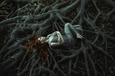 Katerina Klio WOMAN WITH RED HAIR LYING ON TREE ROOTS Women