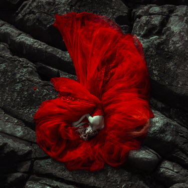 Katerina Klio WOMAN IN RED DRESS LYING ON ROCKS Women