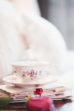 Stephanie Frey Steaming cup of tea in a pretty teacup on a stack of letters with rose flower in foreground.